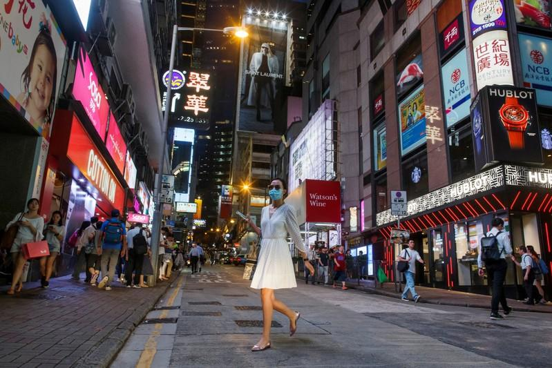 FILE PHOTO: A woman crosses a street in the Central business district in Hong Kong