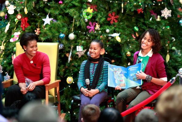 First lady Michelle Obama and her daughters Sasha (C) and Malia read Christmas stories to children at the Children's National Medical Center on December 22, 2009 in Washington, DC. The first lady toured the hospital visiting the Heart and Kidney Unit before greeting 200 patients and hospital staff. (Photo by Mark Wilson/Getty Images)