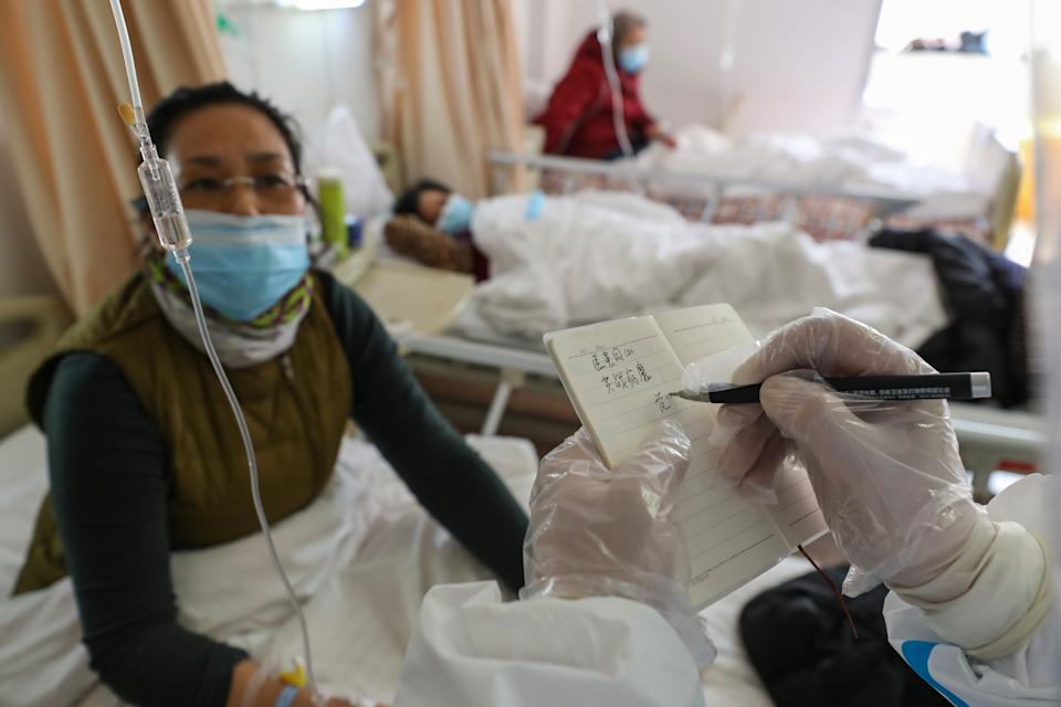 WUHAN, CHINA - FEBRUARY 25 2020: Dr. Fan Zhongjie, a respiratory specialist in charge of about 30 critical COVID-19 patients in his section, writes encouraging words for a patient in a hospital in Wuhan in central China's Hubei province Tuesday, Feb. 25, 2020. After the hospital was designated for COVID-19 patients and doctors and nurses of other disciplines were all assigned to respiratory patients, he has also to oversee his colleagues' jobs and help them.- PHOTOGRAPH BY Feature China / Barcroft Studios / Future Publishing (Photo credit should read Feature China/Barcroft Media via Getty Images)