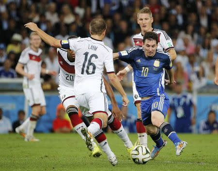Argentina's Lionel Messi is challenged by Germany's Jerome Boateng and Philipp Lahm during their 2014 World Cup final at the Maracana stadium in Rio de Janeiro July 13, 2014. REUTERS/Sergio Moraes