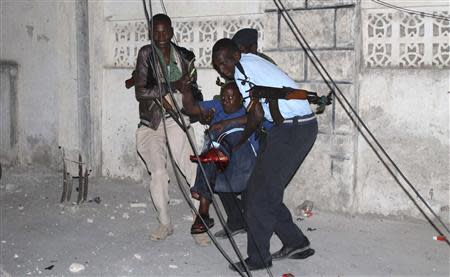 Police officers carry an injured man from the scene of a bomb attack outside the Jazira hotel in Mogadishu January 1, 2014. REUTERS/Feisal Omar