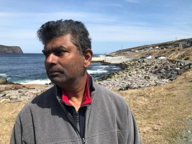 Don Jayasinghe stands near a search and rescue operation on Thursday afternoon in Flatrock, N.L., a day after his son, Supul, slipped on rocks near the water and fell in. (Terry Roberts/CBC - image credit)