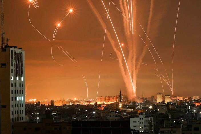 Light trails of rockets fired at Israel from the Gaza Strip, lighting up the orange night sky