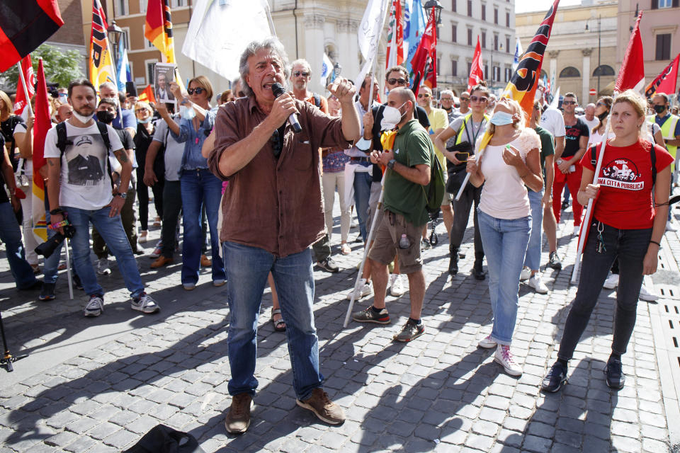 """Alitalia workers stage a protest in Rome, Tuesday, Sept. 21, 2021. Italy's failing national carrier Alitalia told passengers on Tuesday to just bring a single piece of hand luggage when travelling, given intensifying strikes and labor protests are disrupting service ahead of the airline's Oct. 14 demise. In a series of Tweets, Alitalia apologized to its customers and blamed the disruptions on union meetings that """"over the coming days could result in delays in the services provided by Alitalia."""" (Roberto Monaldo/LaPresse via AP)"""