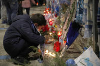 A boy lights a candle as people gather outside the San Paolo Stadium to pay their homage to soccer legend Diego Maradona, in Naples, Italy, Wednesday, Nov. 25, 2020. Diego Maradona has died. The Argentine soccer great was among the best players ever and who led his country to the 1986 World Cup title before later struggling with cocaine use and obesity. He was 60. (AP Photo/Alessandra Tarantino)