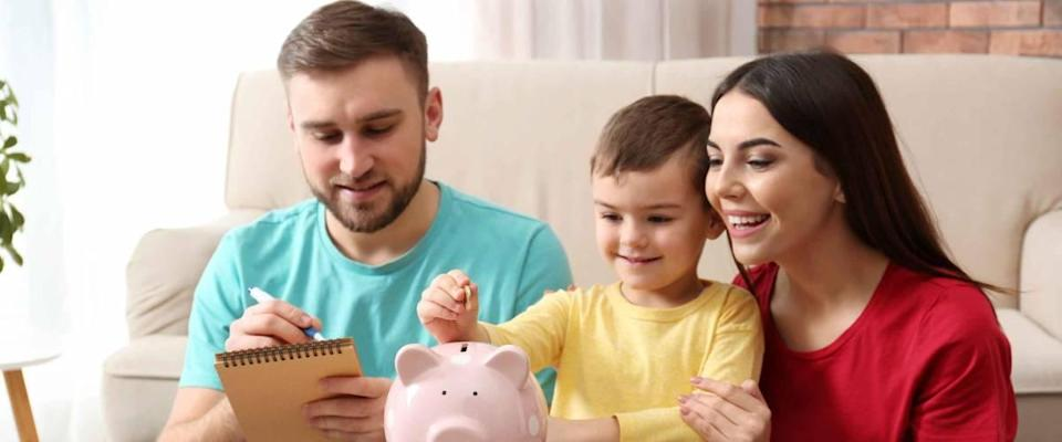 Happy family with piggy bank and money at home