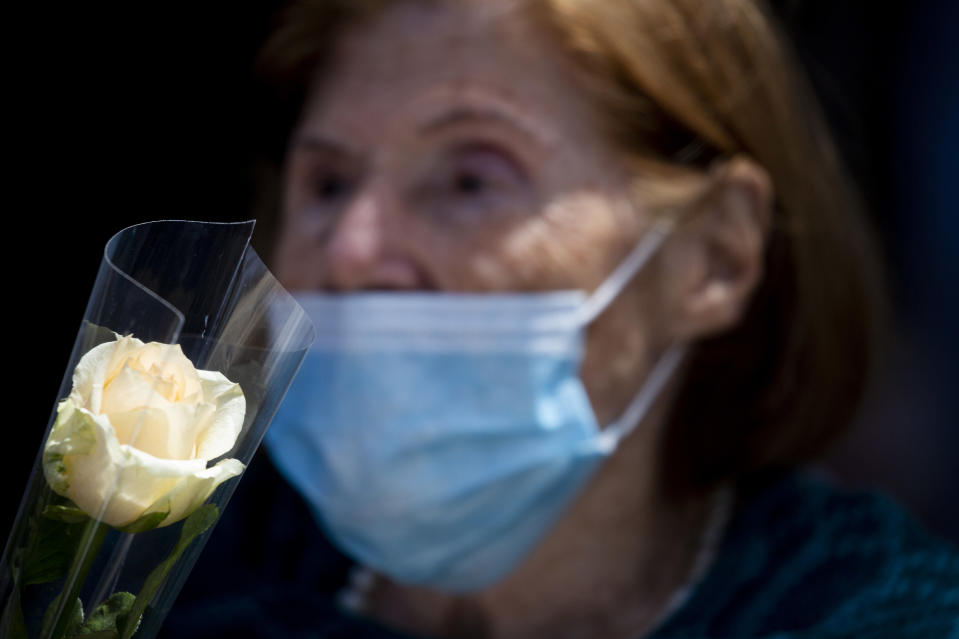 Holocaust survivor Fanny Amar wearing a face mask amid the coronavirus holds a rose as she and others attend the yearly Holocaust Remembrance Day ceremony in Haifa, Israel, Thursday, April 8, 2021. (AP Photo/Ariel Schalit)