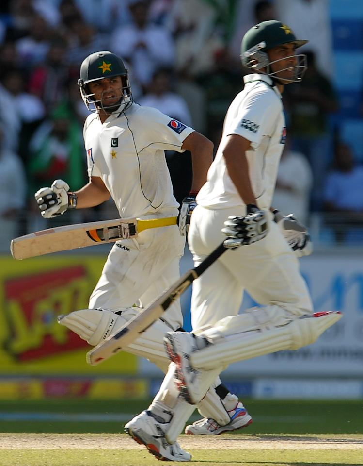 Pakistan's cricketers Younis Khan (R) and Azhar Ali (L) run between the wickets during the second day of the third and final Test match between Pakistan and England at the Dubai International Cricket Stadium at Dubai Sports City on February 4, 2012.  England were bowled out for 141 in their first innings on the second day of the third and final Test that gives them a 42-run lead over Pakistan's first innings total of 99.  AFP PHOTO/ LAKRUWAN WANNIARACHCHI (Photo credit should read LAKRUWAN WANNIARACHCHI/AFP/Getty Images)