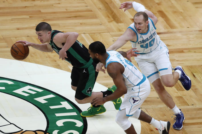 Boston Celtics' Payton Pritchard (11) breaks away from Charlotte Hornets' Cody Zeller (40) and Brad Wanamaker (9) during the first half of an NBA basketball game Sunday, April 4, 2021, in Boston. (AP Photo/Michael Dwyer)