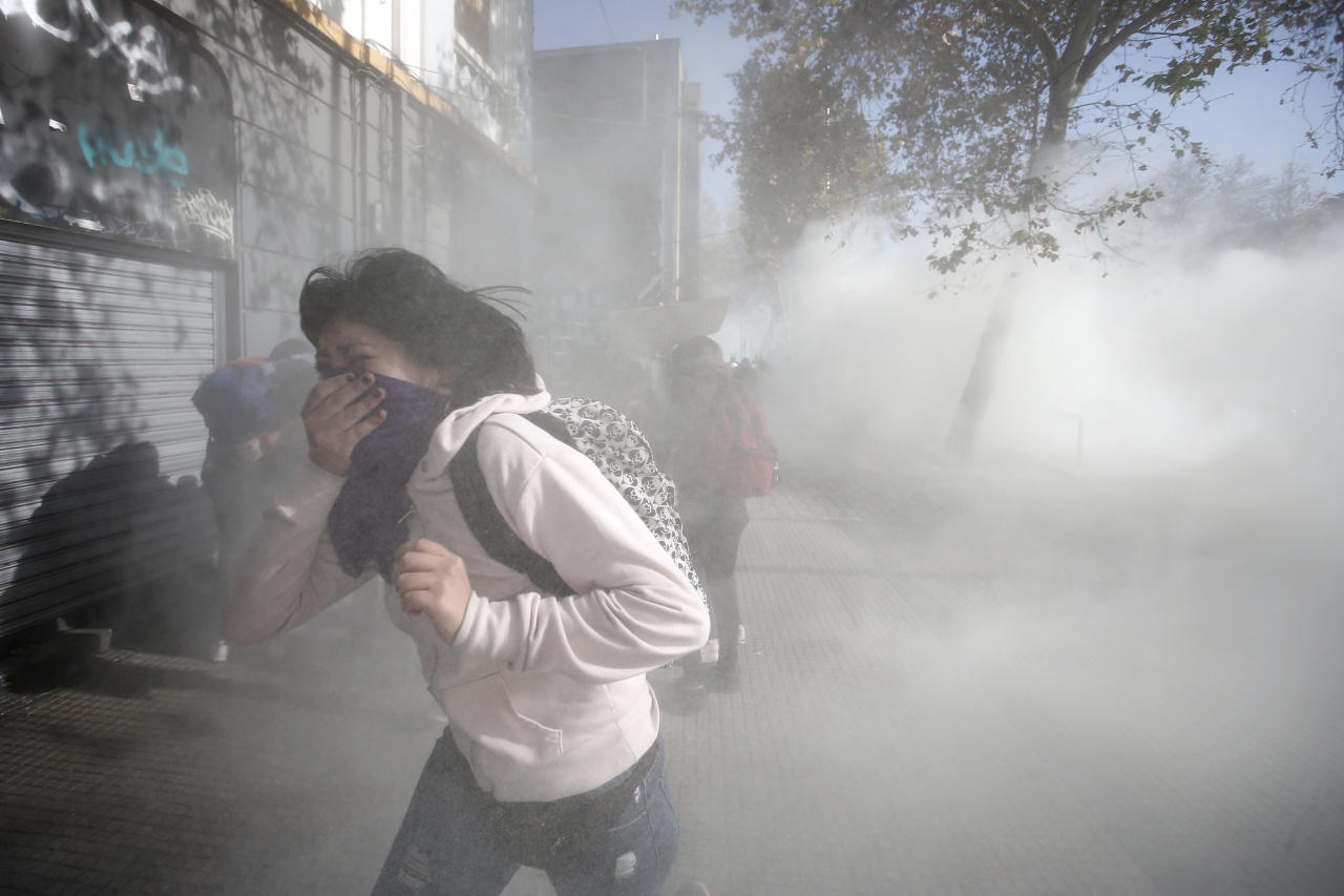 A woman runs as police launch tear gas to disperse a group of hooded protesters, at the end of peaceful march demanding an end to what they say is sexist education and sexual harassment in Chilean universities, in Santiago, Chile, Wednesday, June 6, 2018. (AP Photo/Luis Hidalgo)