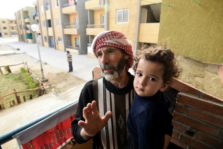 Syrian Mohamed Amin, 43, who fled his country with his family due to the war, stands with his child next to a baking-oven at a make-shift bakery set up on the balcony of his apartment in Cairo