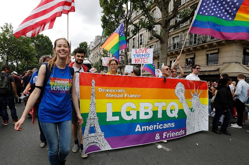 "Participants hold a ""Democrats Abroad"" banner and US and rainbow flags during the Gay Pride parade in Paris on July 2, 2016 (AFP Photo/Francois Guillot)"