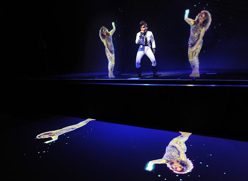 CORRECTS NAME OF EVENT FROM AUDI M3 TO AUDI A3 Janelle Monae, center, performs alongside holograms of M.I.A. during a launch party for the Audi A3 on Thursday, April 3, 2014 in West Hollywood, Calif. (Photo by Chris Pizzello/Invision/AP)