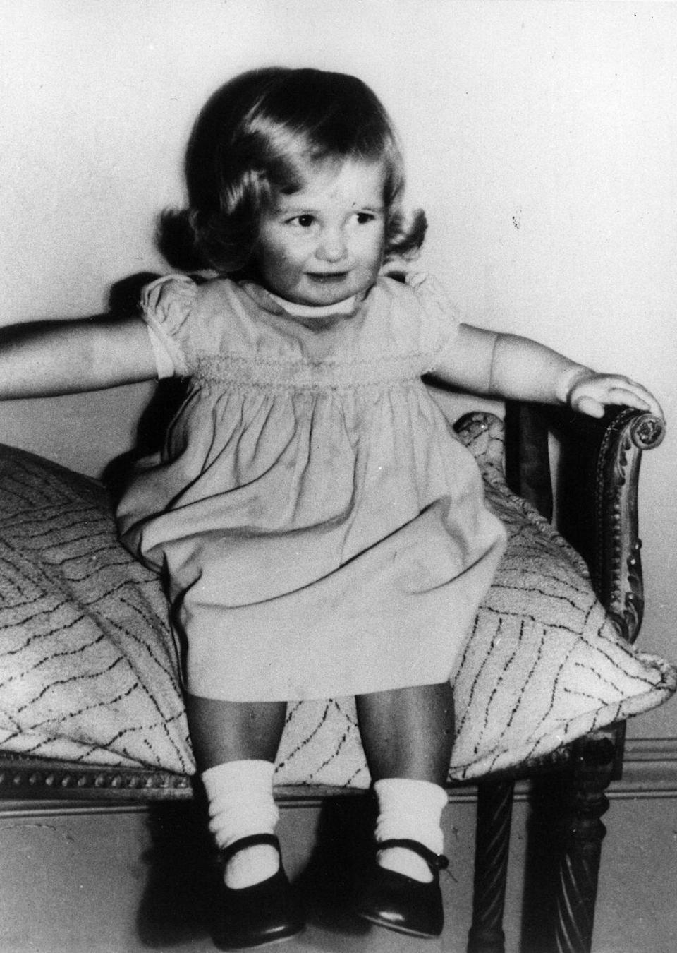 <p>In 1963, the adorable future royal posed for a photograph with precious curly hair and Mary Jane shoes. </p>