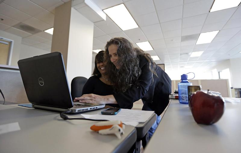 In this Aug. 15, 2013, photo, Michelle Nicolosi, right, helps Stephanie Weldy with a laptop as the staff of the Long Beach Register prepares for its first day of publication at its office in Long Beach, Calif. Published by the Orange County Register, the Long Beach Register makes its five-day-a-week debut Monday, Aug. 19. It's the first expansion of the Register outside of Orange County under new owners Aaron Kushner and Eric Spitz, who bought the newspaper's parent company, Freedom Communications Inc., last year. The Long Beach Register will have a newsroom staff of 20 and seek to compete with the established newspaper in town, the Long Beach Press-Telegram. (AP Photo/Reed Saxon)