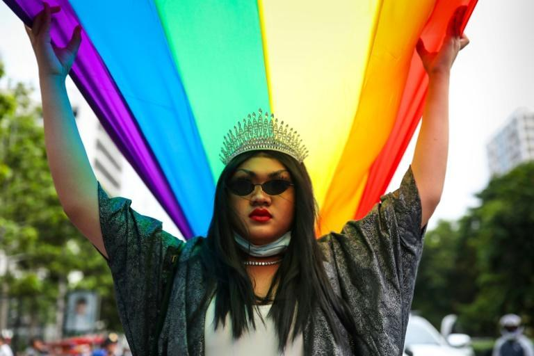 An LGBTQ activist helps hold a giant rainbow flag during the Pride Parade in Bangkok