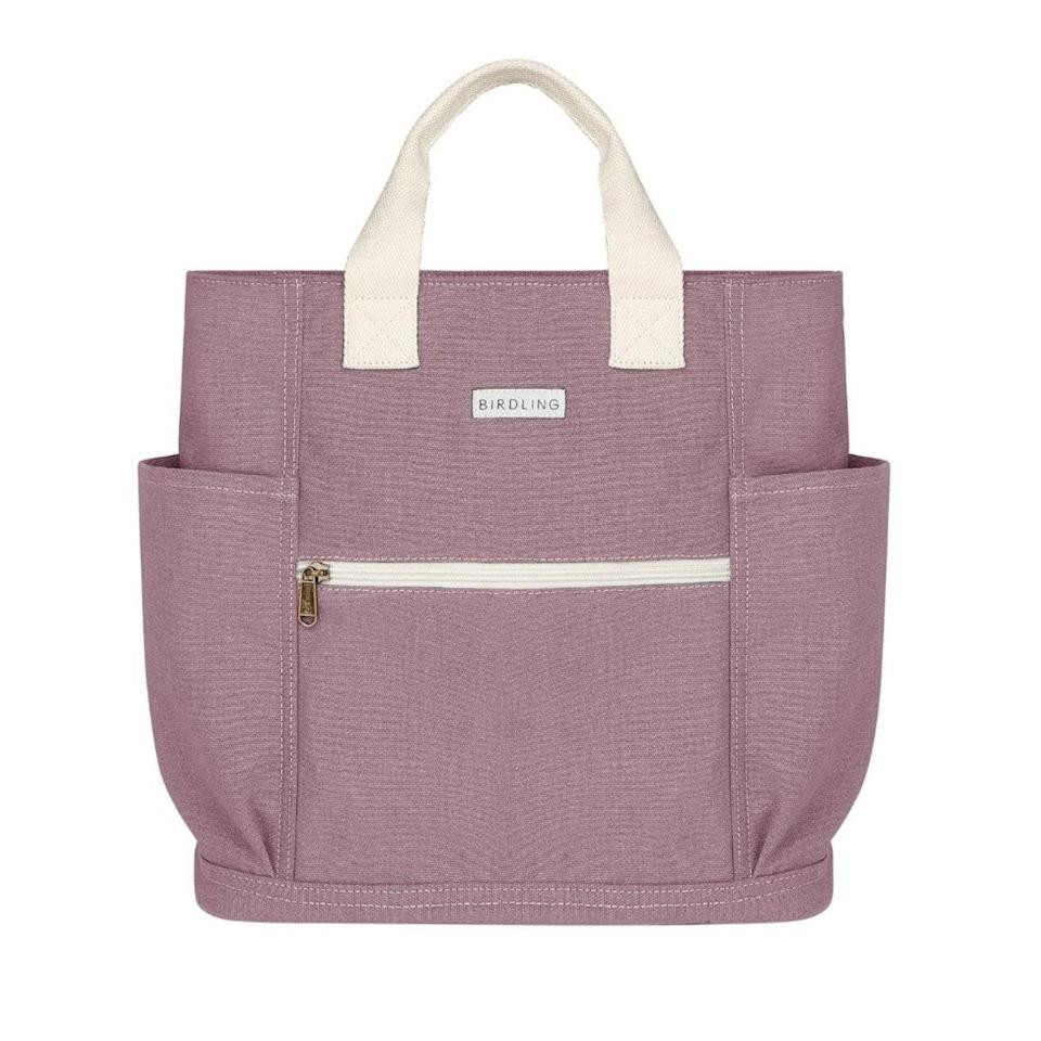 """We chose this bag because it doesn't look like a diaper bag. It's neutral-toned and unassuming in that Herschel backpack kind of way. And the inside is extremely handy for baby things. In the central compartment, I keep a travel <a href=""""https://www.glamour.com/gallery/best-white-noise-machine?mbid=synd_yahoo_rss"""" rel=""""nofollow noopener"""" target=""""_blank"""" data-ylk=""""slk:white noise machine"""" class=""""link rapid-noclick-resp"""">white noise machine</a>, stacking cups, a swaddle, some Lovevery cards, and a little music player. Then, in one of the side compartments, I keep all the diaper essentials. On the other side, there's two more compartments. I stick a travel <a href=""""https://www.glamour.com/story/where-to-buy-first-aid-kit?mbid=synd_yahoo_rss"""" rel=""""nofollow noopener"""" target=""""_blank"""" data-ylk=""""slk:first aid kit"""" class=""""link rapid-noclick-resp"""">first aid kit</a> in one and then currently there's a pair of disposable latex gloves—to give you an idea of when during the course of the pandemic I gave birth. In the front pocket, we have a little bottle of <a href=""""https://www.glamour.com/gallery/where-to-buy-hand-sanitizer?mbid=synd_yahoo_rss"""" rel=""""nofollow noopener"""" target=""""_blank"""" data-ylk=""""slk:hand sanitizer"""" class=""""link rapid-noclick-resp"""">hand sanitizer</a>. Lastly, there are two bottle holders on either side of the bag. This has been clutch for feeding on the go—I can have a thermos of milk in one and a bottle in the other. Before our baby transitioned to whole milk, I'd keep a bottle with powder formula in one and a thermos of warm water in the other. In short: It's a backpack/tote that doesn't look like a diaper bag, even though it's painfully obvious it's a diaper bag because...we have a baby. —<em>Maura Lynch, writer and editor and mom of one</em> $68, Birdling. <a href=""""https://birdling.com/products/backpack-new"""" rel=""""nofollow noopener"""" target=""""_blank"""" data-ylk=""""slk:Get it now!"""" class=""""link rapid-noclick-resp"""">Get it now!</a>"""