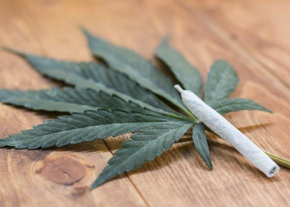 A rolled cannabis joint lying atop a cannabis leaf on a table.
