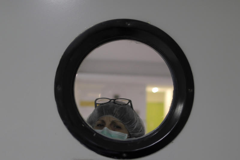 A health worker wearing a face mask to protect from coronavirus, looks out of from a window at a nursing home in Madrid, Spain, Tuesday, March 31, 2020. The new coronavirus causes mild or moderate symptoms for most people, but for some, especially older adults and people with existing health problems, it can cause more severe illness or death. (AP Photo/Manu Fernandez)