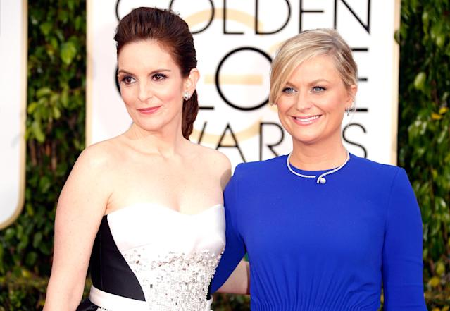 Hosts Tina Fey (L) and Amy Poehler attend the 72nd Annual Golden Globe Awards at The Beverly Hilton Hotel on January 11, 2015 in Beverly Hills, California. (Photo by Jeff Vespa/WireImage)