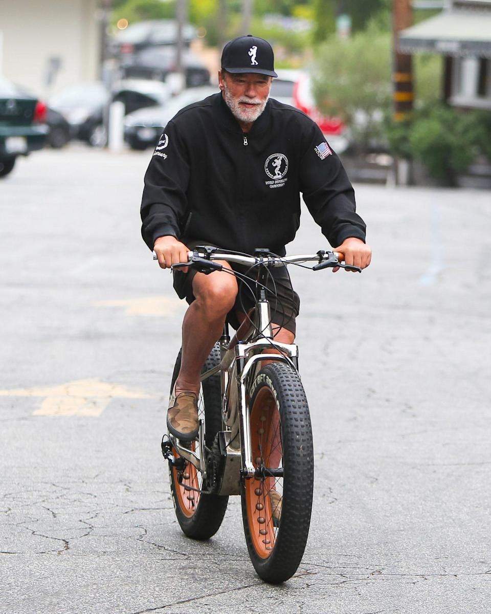 <p>Arnold Schwarzenegger takes a solo spin around his Los Angeles neighborhood on Wednesday.</p>