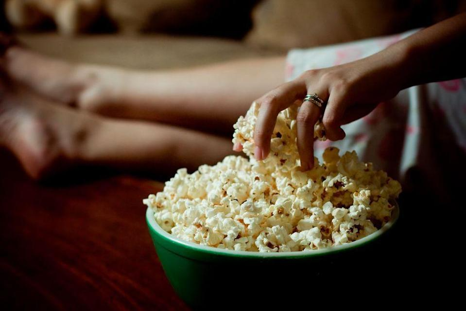 """<p>Sometimes you just need a salty, crunchy snack, you know? When the cravings hit, heat some corn kernels over the stove and make a bowl of popcorn. """"Popcorn is a high fiber snack that often gets a bad rep,"""" registered dietitian <a href=""""https://www.claudiahleap.com/"""" rel=""""nofollow noopener"""" target=""""_blank"""" data-ylk=""""slk:Claudia Hleap"""" class=""""link rapid-noclick-resp"""">Claudia Hleap</a>, LDN, tells Delish. """"Popcorn is a whole grain, making it a good source of fiber. It's also full of popped air, meaning that it is less calorie dense than many other chip-like options."""" <br></p>"""