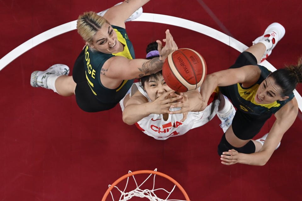 China's Yueru Li, center, drives to the basket between Australia's Cayla George,left, and Bec Allen, right, during a women's basketball game at the 2020 Summer Olympics, Wednesday, July 28, 2021, in Saitama, Japan. (Aris Messinis/Pool Photo via AP)