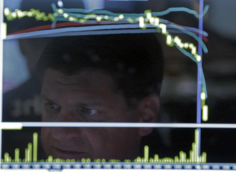 Specialist Michael Guli is reflected in a screen at his post on the floor of the New York Stock Exchange, Thursday, June 20, 2013. Financial markets are sliding after the Federal Reserve said it could end its huge bond-buying program by the middle of next year. (AP Photo/Richard Drew)