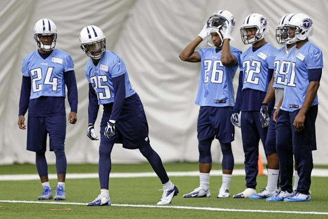 Tennessee Titans cornerbacks Coty Sensabaugh (24) and Blidi Wreh-Wilson (25) run a drill with other defensemen during NFL football minicamp Monday, June 9, 2014, in Nashville, Tenn. Sensabaugh and Wreh-Wilson are competing to replace cornerback Alterraun Verner, who signed with Tampa Bay in free agency. (AP Photo/Mark Humphrey)