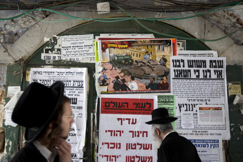 "In this Sunday, July 14, 2013 photo, ultra-Orthodox Jewish men walk past a poster in the ultra-Orthodox Jewish Mea Shearim neighborhood in Jerusalem. A large cartoon poster depicts Haredi soldiers rolling through the streets atop tanks trying to lure young boys onto their vehicles. The ad denounces the soldiers as Zionist ""ambassadors"" and ""missionaries."" The soldiers in sidecurls have been coined the insulting nickname ""Hardak"" _ a combination of Haredi and insect. (AP Photo/Sebastian Scheiner)"