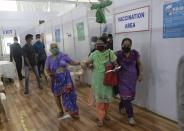 A woman leaves after receiving her second dose of the COVID-19 vaccine at a vaccination center that is closed for fresh registrations for first doses because of shortage the vaccine, in Mumbai, India, Friday, April 9, 2021. India has a seven-day rolling average of more than 100,000 cases per day and has reported 13 million virus cases since the pandemic began, the third-highest total after the United States and Brazil. (AP Photo/Rajanish Kakade)