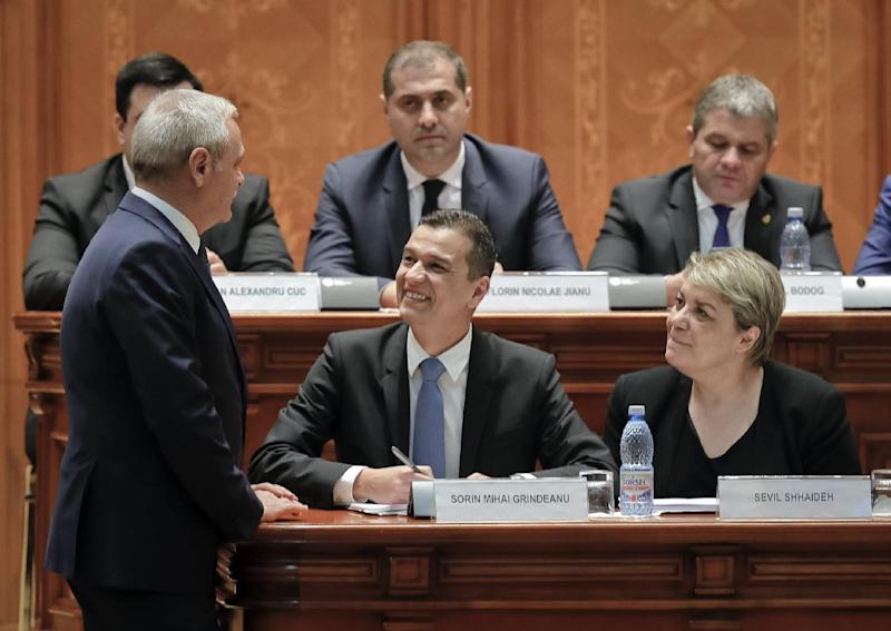 """Romanian Prime Minister designate Sorin Grindeanu, center, smiles at Liviu Dragnea, the leader of the Social Democrat party, left, before a parliament session, in Bucharest, Romania, Wednesday, Jan. 4, 2017. Grindeanu said Wednesday he wants to stop thousands of Romanians emigrating, build highways and encourage the consumption of local produce to create what he called """"a normal Romania."""" (AP Photo/Vadim Ghirda)"""
