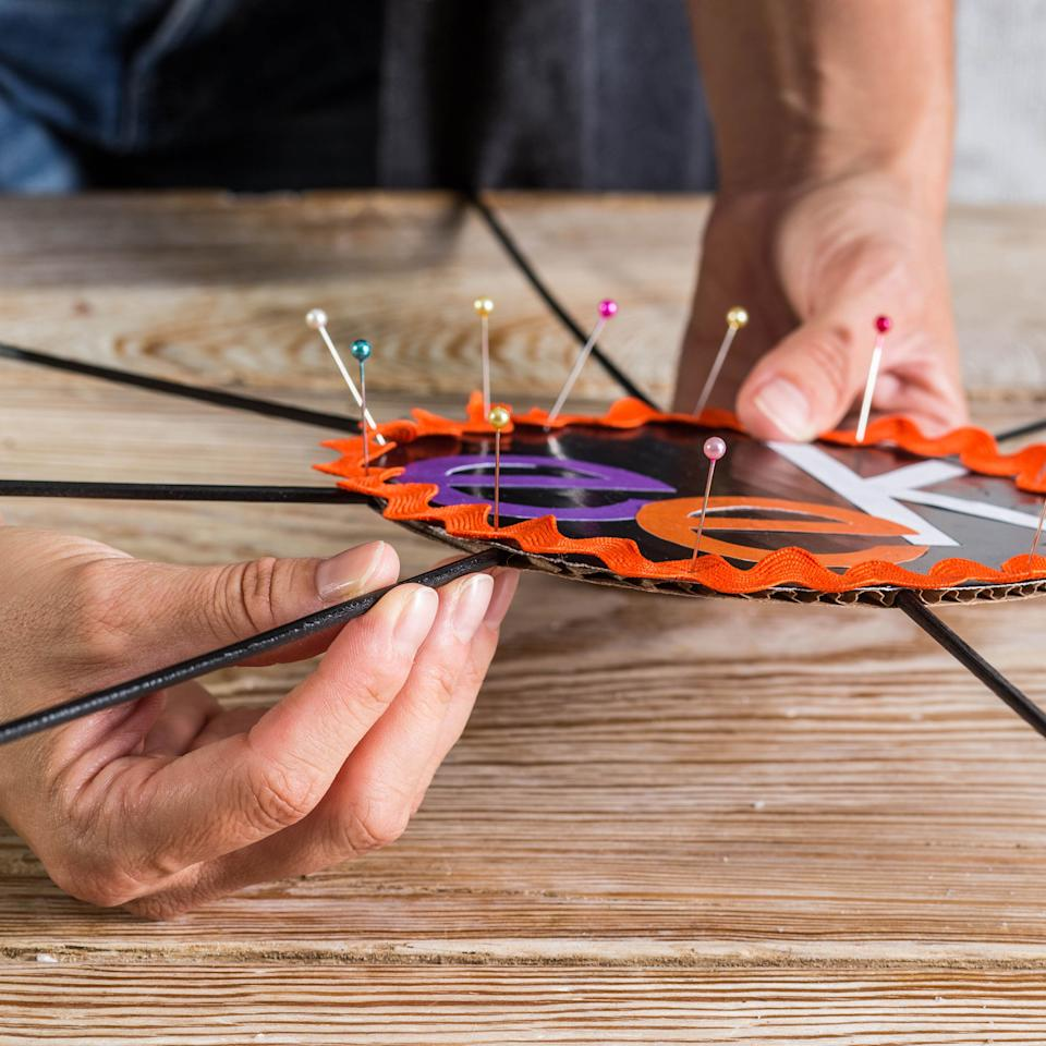 <p>Glue rick rack around outer edge of circle, using straight pins to anchor. Let dry. Insert skewers into edge of cardboard circle, spacing evenly and leaving about 9 inches showing.</p>