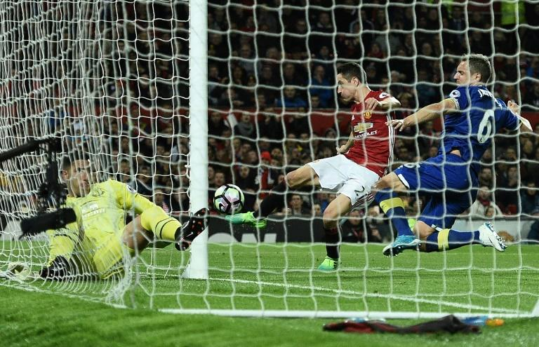 Everton's defender Phil Jagielka (R) jumps to block a shot from Manchester United's midfielder Ander Herrera (C as Everton's goalkeeper Joel Robles lays in his goal injured during the English Premier League football match on April 4, 2017