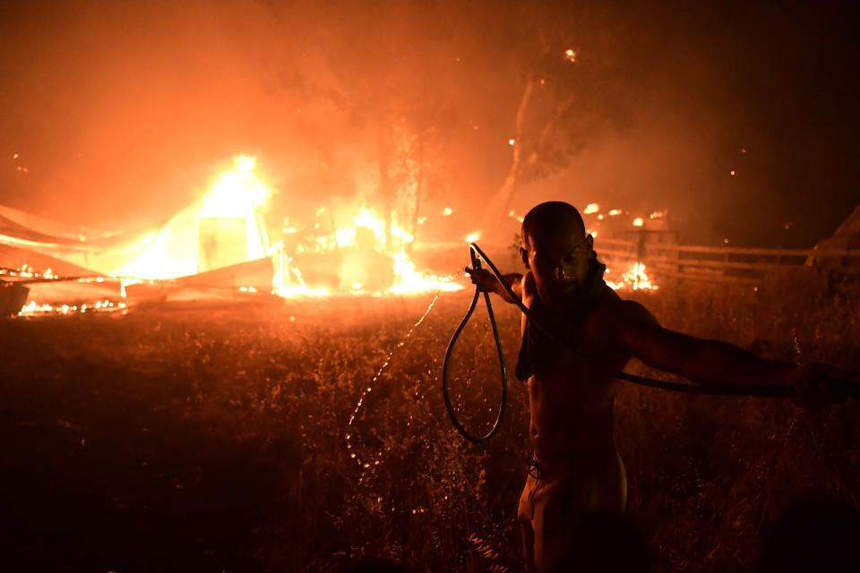 A man uses a water hose during a wildfire in Adames area, in northern Athens, Greece, Tuesday, Aug. 3, 2021.Thousands of people fled their homes north of Athens on Tuesday as a wildfire broke out of the forest and reached residential areas. The hurried evacuations took place just as Greece grappled with its worst heat wave in decades. (AP Photo/Michael Varaklas)
