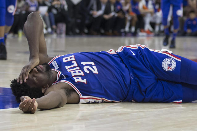 PHILADELPHIA, PA - MARCH 28: Joel Embiid #21 of the Philadelphia 76ers lies on the court after a collision with Markelle Fultz #20 of the Philadelphia 76ers in the second quarter against the New York Knicks at the Wells Fargo Center on March 28, 2018 in Philadelphia, Pennsylvania. (Photo by Mitchell Leff/Getty Images)