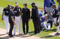 Chicago White Sox's Jose Abreu, left, heads to the dugout as Kansas City Royals' Hunter Dozier tries to get up after they collided along the first base line in the second inning of the first game of a baseball doubleheader Friday, May 14, 2021, in Chicago. (AP Photo/Charles Rex Arbogast)