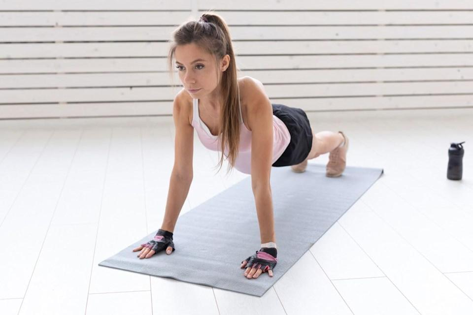 a young woman is doing fitness in the gym or home. She is pressing in the sport suit