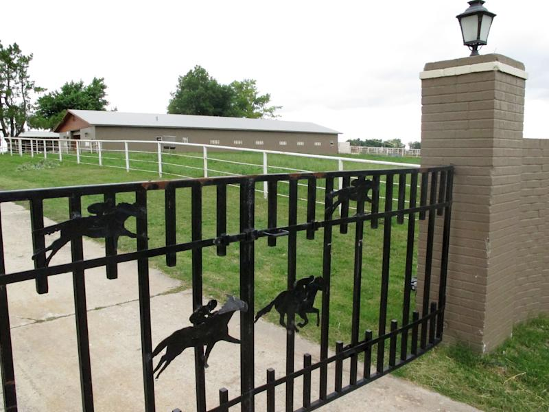 An iron gate gate is seen at the Jose Trevino Morales's stables Wednesday, June 13, 2012, in Lexington, Okla. On Tuesday, authorities raided the ranch accusing Trevino and others of running a sophisticated money-laundering operation connected to one of Mexico's most powerful and ruthless drug cartels. (AP Photo/Sean Murphy)