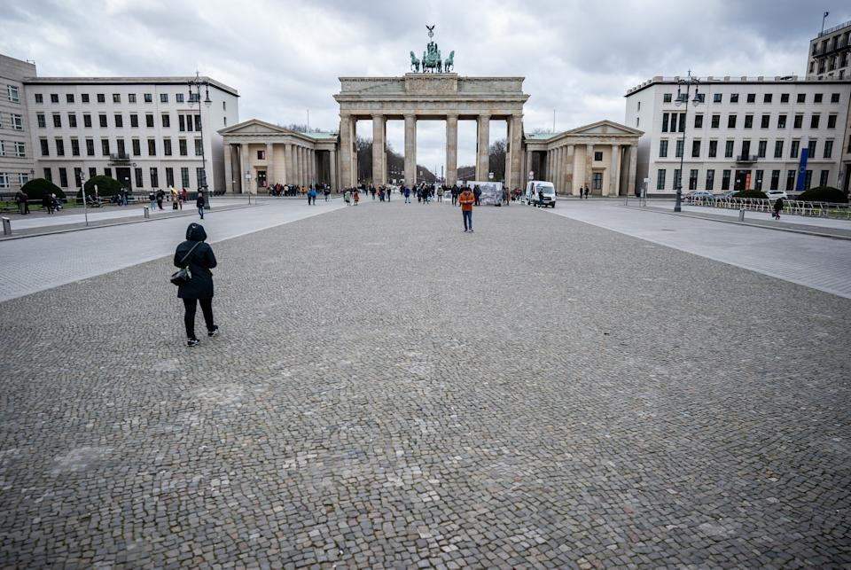 13 March 2020, Berlin: Only a few tourists stand on the Pariser Platz at the Brandenburg Gate. Photo: Michael Kappeler/dpa (Photo by Michael Kappeler/picture alliance via Getty Images)