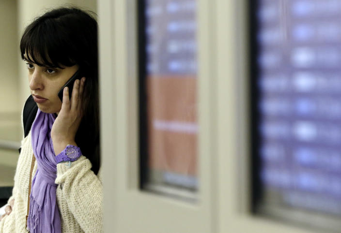 A passengers reacts as she talks on her phone at Midway airport in Chicago, Thursday, Dec. 20, 2012. The first widespread snowstorm of the season crawled across the Midwest on Thursday, with whiteout conditions stranding holiday travelers. The storm led airlines to cancel about 1,000 flights ahead of the Christmas holiday — relatively few compared to past big storms, though the number was climbing. Southwest Airlines scratched all of its flights scheduled after 4:30 p.m. today at Midway. (AP Photo/Nam Y. Huh)