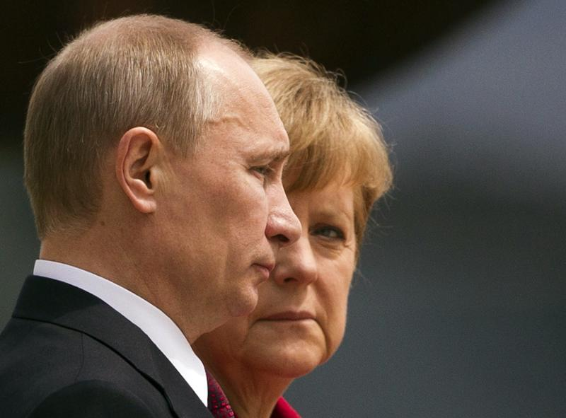 German Chancellor Angela Merkel looks at Russian President Vladimir Putin (L) as they listen to their national anthems before talks at the Chancellery in Berlin, in this June 1, 2012 file photo. Heavily dependent on Russian gas and closer to Moscow than any other leading western nation, Germany faces a major policy dilemma as the Ukraine crisis descends into a Cold War-style confrontation of tit-for-tat threats and ultimatums. For weeks, Merkel and her three-month old coalition government have gone out of their way to avoid antagonising Putin, remaining measured even as Washington and other capitals ratcheted up the rhetoric. REUTERS/Thomas Peter/Files (GERMANY - Tags: POLITICS CIVIL UNREST)