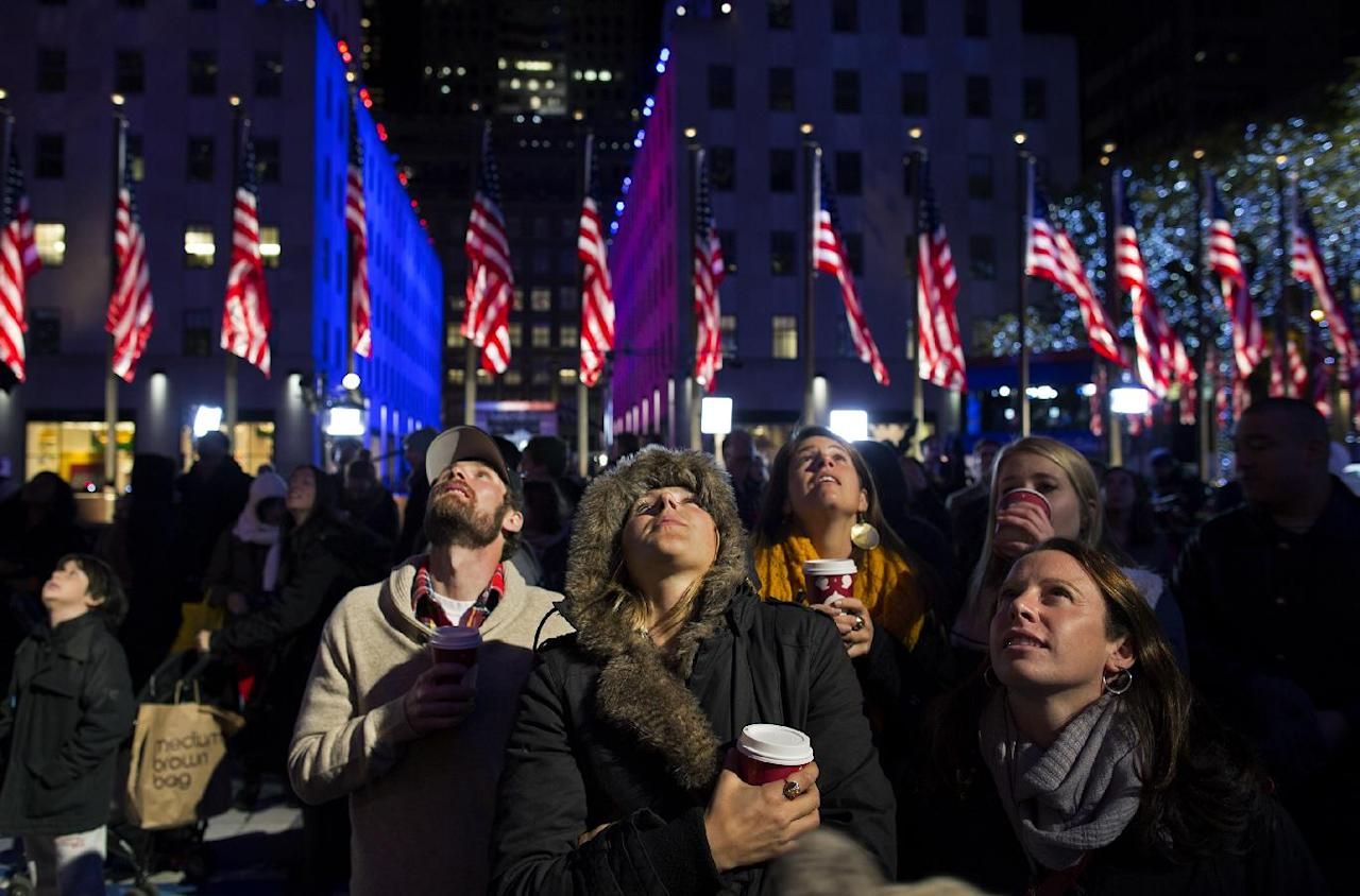 People watch election results displayed on a utility lift suspended from the front of the GE Building at Rockefeller Center, in New York, Tuesday, Nov. 6, 2012. From center left are Bryan Fletcher of Park City, Utah; Jen Hudak, Salt Lake City; Lindsay Arnold, Park City; K.C. Oakley, Park City, and Emily Cook, Park City. After a year of campaigning, polls have begun to close after Americans across the United States headed to the polls to decide the winner of the tight presidential race between President Barack Obama and Republican presidential candidate, former Massachusetts Gov. Mitt Romney. (AP Photo/Craig Ruttle)
