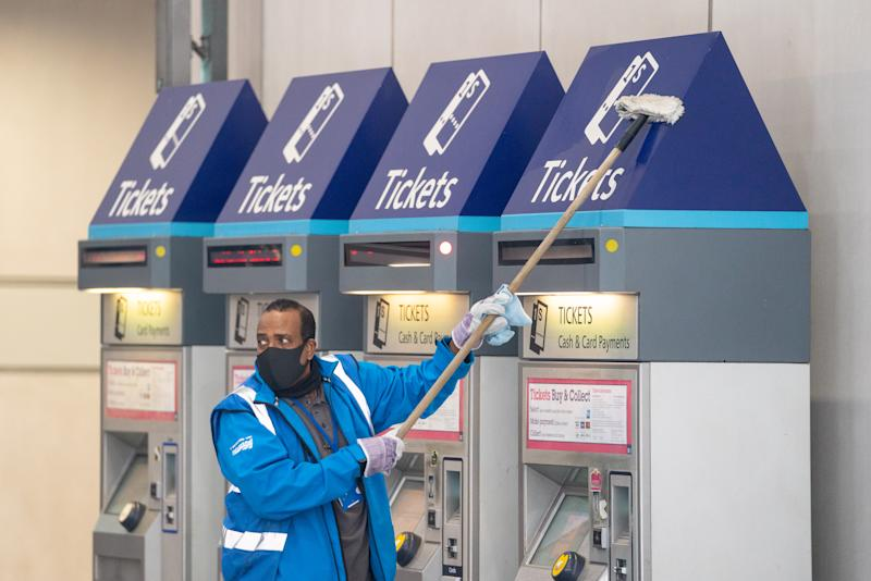 A member of staff wearing a protective face mask cleans ticket machines at London Bridge station in London, as train services increase as part of the easing of coronavirus lockdown restrictions. (Photo by Dominic Lipinski/PA Images via Getty Images)