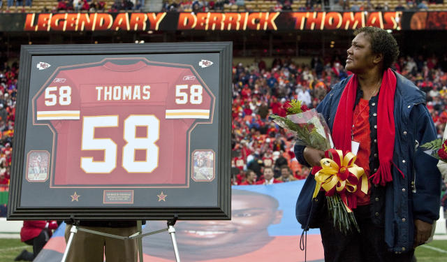 "Edith Morgan, mother of <a class=""link rapid-noclick-resp"" href=""/nfl/teams/kan/"" data-ylk=""slk:Kansas City Chiefs"">Kansas City Chiefs</a> Hall of Fame player Derrick Thomas, looks at his framed jersey during a half-time ceremony. (Getty)"