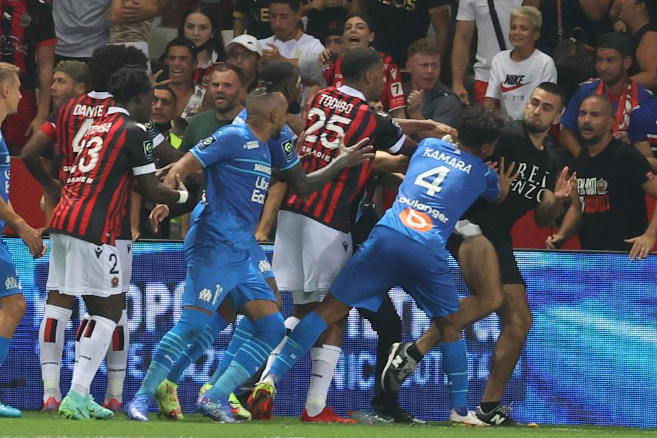Marseille's French midfielder Dimitri Payet (2nd L) reacts as players from OGC Nice (red and black jersey) and Olympique de Marseille (blue jersey) stop a fan invading the pitch  during the French L1 football match between OGC Nice and Olympique de Marseille (OM) at the Allianz Riviera stadium in Nice, southern France on August 22, 2021. - The French Ligue 1 game between Nice and Marseille was halted on August 22, 2021, when fans of the home side invaded the pitch and angrily confronted opposing player Dimitri Payet. An AFP journalist at the game said trouble flared in the 75th minute when Marseille star Payet, who had been targeted by plastic bottles every time he took a corner, lobbed one back into the stands. (Photo by Valery HACHE / AFP) (Photo by VALERY HACHE/AFP via Getty Images)
