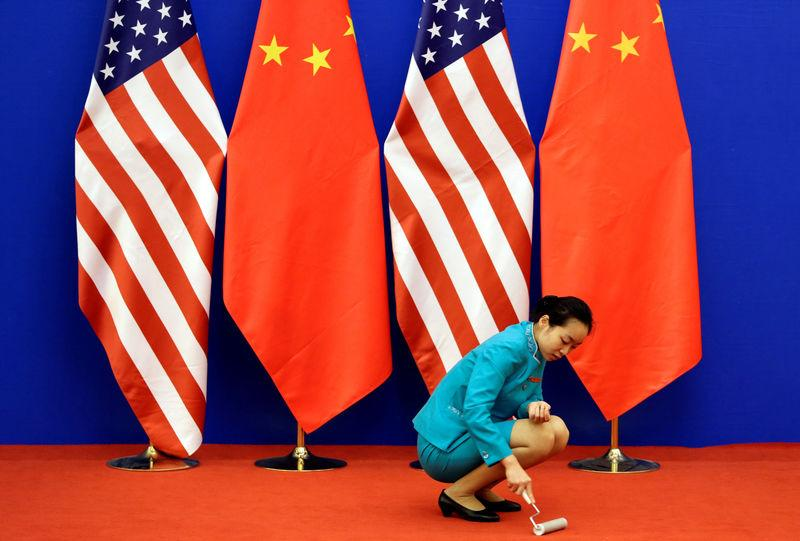 FILE PHOTO: An attendant cleans the carpet next to U.S. and Chinese national flags before a news conference for the 6th round of U.S.-China Strategic and Economic Dialogue at the Great Hall of the People in Beijing