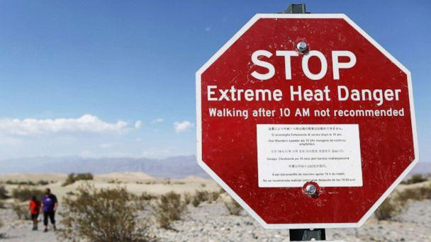 PHOTO: Visitors walk near a sign warning of extreme heat danger in Death Valley National Park, Calif., on Aug. 17, 2020. The temperature in the park reached 130 degrees on Aug. 16, one of the highest temperatures ever recorded. (Mario Tama/Getty Images)