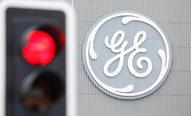 A traffic light is seen in front of a logo of General Electric at the company's plant in Birr
