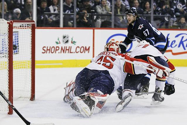 Winnipeg Jets' Michael Frolik (67) scores on Florida Panthers goaltender Jacob Markstrom, left, and Dmitry Kulikov (7) during the second period of an NHL hockey game in Winnipeg, Manitoba on Friday, Dec. 20, 2013. (AP Photo/The Canadian Press, John Woods)